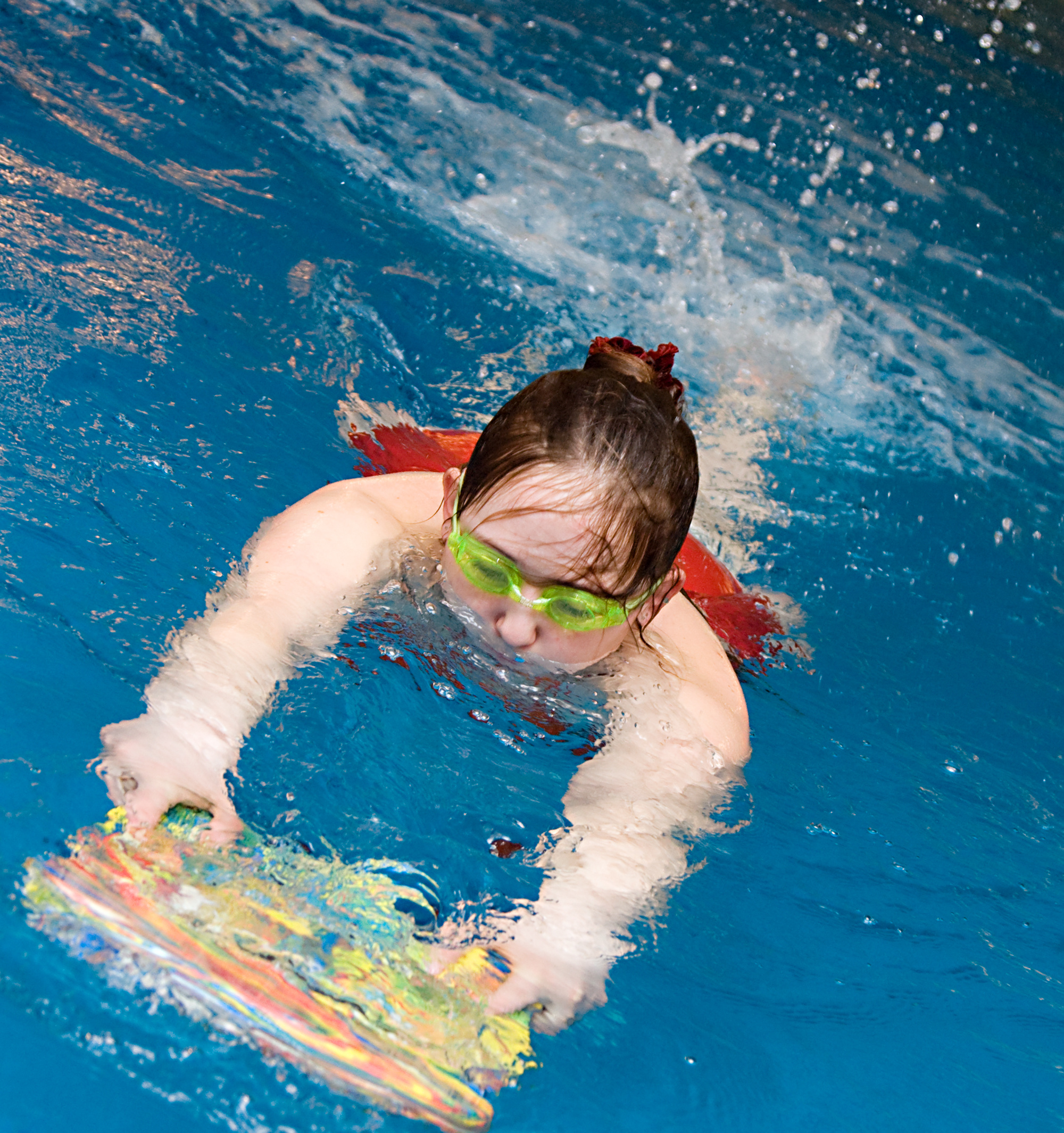 girl learn to swimm with board in the swimming pool