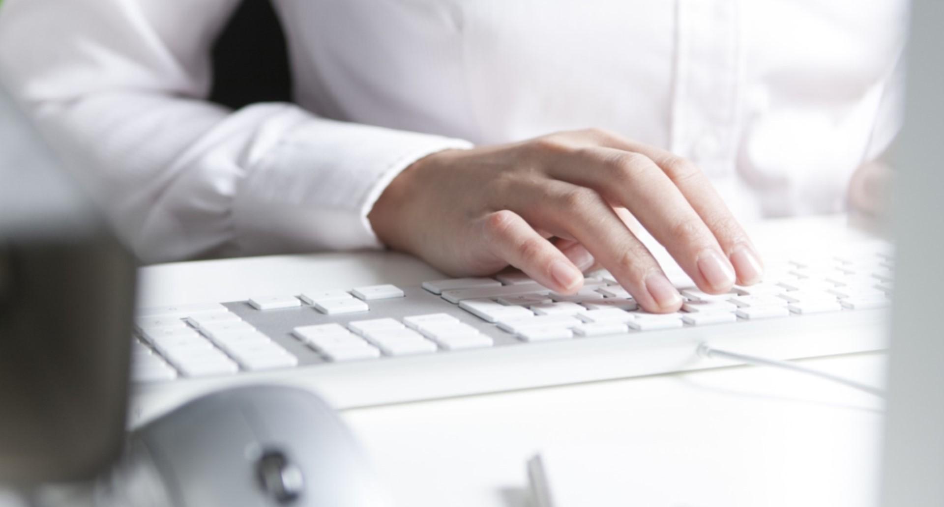 Frau arbeitet am Schreibtisch, Tastatur